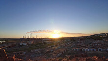 An Epic Sunset With A View Of The Smoke Of The Factory. There Are Garages And Small Houses. Near The Beach Of Lake Balkhash. There Are Many Swifts And Different Birds Flying. Ecology. Air Pollution
