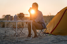 Sunset Scenic View Of Woman Holding Metal Glass. Foldable Camping Gas Fire System With A  Pot On A Table.