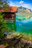 Scenic of a wooden boat house , the mountains and the lake