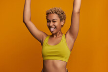 Horizontal Studio Image Of Funny Youthful Mixed-race Fitness Girl In Yellow, Posing With Sticking Tongue, Teasing Face Expression, Looking Carefree Putting Hands Up. People And Sport
