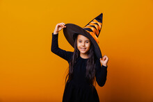 Little Cheerful Caucasian Girl In Halloween Witch Costume Isolated On Yellow Background.