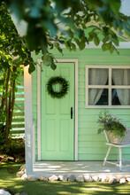 Green Door And Decorative Wreath. Autumn Welcome Wreath, Decorating Front Door Home. House Door With Decor With Leaves Wreath. Autumn Cozy Decor Home For Thanksgiving. Summer Decor Door
