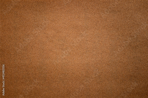 Photo Sandpaper texture background where you can see the red-brown sand grain pattern on the sandpaper, suitable as a background for inserting text