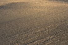 Holidays By The Sea, Sand On The Beach And Gentle Waves. The Setting Sun Is Reflected In The Golden Sand Of The Beach