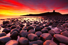 Sunrise At Embleton Beach With Dunstanburgh Castle In The Background, Northumberland, England, UK.
