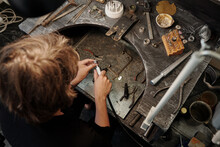 High Angle View Of Jeweler Using Abrasive Tool While Polishing Silver Ring On Work Station
