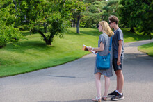 Mother And Son Looking At A Map Along A Urban Pathway