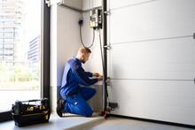 Garage Door Installation And Repair At Home. Contractor Man