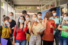 Group Of Students Putting On Or Taking Off Their Face Masks. Young People Of Various Ethnicities Take Safety Measures Against The Covid Virus. Back To School.