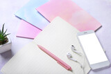 Fototapeta Kawa jest smaczna - Notebooks, pen, mobile phone and earphones on color background, closeup