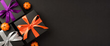 Top View Photo Of Three Black Gift Boxes With Violet Orange And White Ribbon Bows And Small Pumpkins On Isolated Black Background With Copyspace