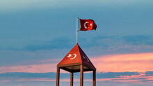 Turkish Flag Over A Top Of Turkish Flag Painted Structure, Waving At Sunset Sky.
