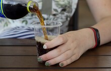 The Girl Pours Coca Cola Into A Glass