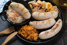 Close-up Of Fried German White Sausages With Stewed Cabbage, Potato Salad And Sauerkraut On A Cast-iron Tray, Studio Shot