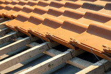 Overlapping Rows Of Yellow Ceramic Roofing Tiles Mounted On Wooden Boards Covering Residential Building Roof Under Construction.