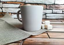 An Ordinary Gray Mug With Three Sugar Cubes On A Napkin On A Brick Background