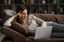 Young Attractive Woman Looking At Laptop Screen, Relaxing On Cozy Couch At Home, Pleasant Millennial Female Enjoying Lazy Leisure Time With Device, Watching Movie, Browsing Apps, Surfing Internet