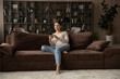 Leinwandbild Motiv Full length woman holding smartphone, sitting on couch at home, attractive young female looking at phone screen, chatting in social networks with friends, shopping, browsing mobile device apps