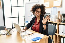 African American Woman With Afro Hair Working At The Office Wearing Operator Headset Waiving Saying Hello Happy And Smiling, Friendly Welcome Gesture
