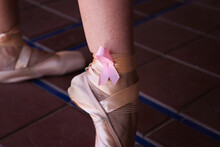 Classical Ballet Dancer's Feet On Points. On The Bow Of The Shoes You Can See A Pink Ribbon In Solidarity With Breast Cancer. Breast Cancer And Classical Ballet Concept