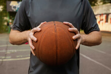 Young Man Holding A Basketball Ball In The Playground. The Concept Of Sports, Active Lifestyle