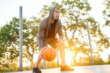 Young Sunlit European Sporty Sportsman Man 20s Wear Sports Clothes Hood Doing Handling Drills Training Holding In Hand Ball Play At Basketball Game Playground Court Outdoor Courtyard Sport Concept