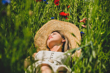 Young Woman In Dress Lying Down On A Grass With Centaurea And Poppy Flowers
