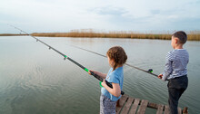 Little Girl And Boy Fish On A Fishing Rod Standing On A Wooden Bridge