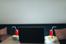 Blank Laptop With Jars Of Juice With Straws And Cups Of Popcorn