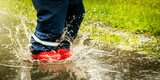 child with red rubber boots jump in puddle on rainy autumn day. waterproof clothing. copy space