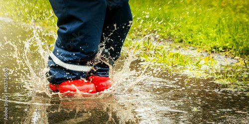 Fotografia child with red rubber boots jump in puddle on rainy autumn day