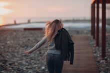 Young Woman Dressed In Jeans And Sweater On The Seashore Pebble Beach