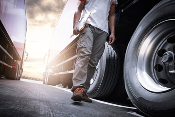 Truck Driver Walking and Checking A Truck Wheels and Tires. Inspection Maintenance and Safety forTruck Driving. Industry Freight Truck.