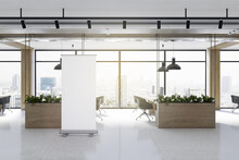 Modern Coworking Office Interior With Empty White Mock Up Poster, Plants In Decorative Wooden Planters, Window With City View, Furniture, Equipment And Daylight. 3D Rendering.