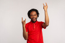 Its Rock N Roll Baby! Portrait Of Bearded Man With Dreadlocks Wearing Red Casual Style T-shirt, Looking At Camera With Rock Sing And Open Mouth. Indoor Studio Shot Isolated On Gray Background.