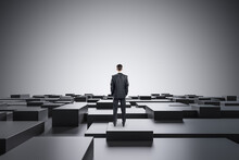 Businessman Standing On Abstract Gray Geometric Maze Background With Mock Up Place. CEO And Future Concept.