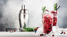 Cranberry Cocktail With Vodka, Ice, Juice, Rosemary And Red Berries In Highball Glass. Refreshing Long Drink. Gray Table Background With Negative Space
