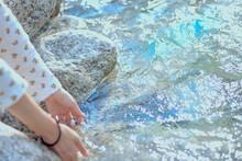 川の冷たい水を触り、爽やかな夏を満喫する女性