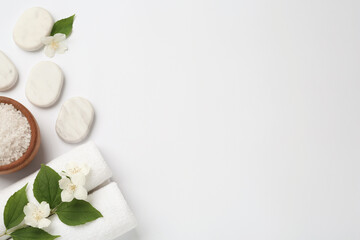 Spa stones, beautiful jasmine flowers, sea salt and towels on white background, flat lay. Space for text