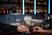 Barman Hand Holding Out Glass With Alcoholic Cocktail To Client