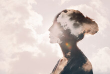 Psychology And Woman Mental Health And Weather Dependent Concept. Multiple Exposure Clouds And Sun On Female Head Silhouette.