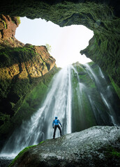 Man in the cave near the Gljufrabui waterfall