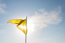 Yellow Flag Flapping In The Wind And Shadowing The Sun,  San Sebastian, Spain. Blue Sky With White Clouds On The Background.