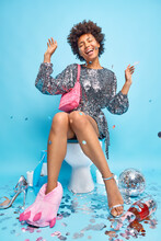 Positive Fashionable Female Model Wears Glittering Dress Carries Small Pink Bag Poses On Toilet Bowl Dances Carefree Surrounded By Confetti Isolated Over Blue Background Has Fun In Lavatory Room