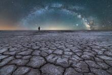 Traveler Standing In Dry Salt Lagoon Against Night Starry Sky