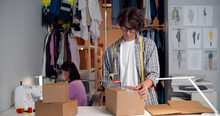 Man Seller Working In Clothing Shop Warehouse Packing Clothes Preparing Parcel For Shipping