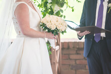 Bride's Hands Holding The Flowers During Exchanging Vows Ceremony