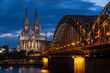 Historical buildings illuminated against blue hour sky late in summer in Cologne