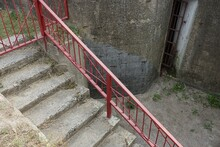 Old Gray Concrete Staircase With Steps With Red Metal Handrails On The Street