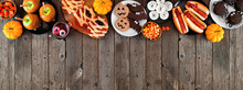 Halloween Party Food Top Border Over A Rustic Wood Banner Background With Copy Space. Above View. Spooky Mummy Pizzas, Finger Hot Dogs, Caramel Apples, Cupcakes, Candy, Cookies And Donuts.